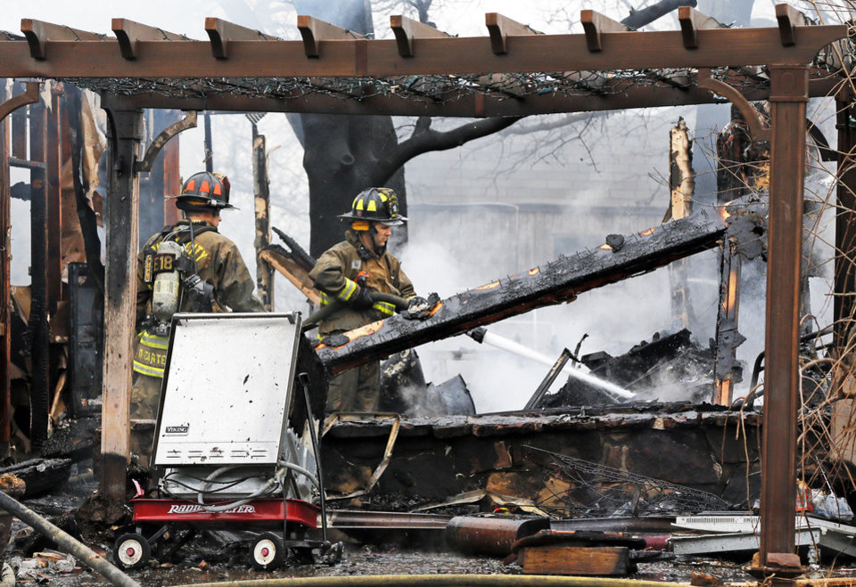 Photo - Oklahoma City firefighters put out hot spots Wednesday at a house fire.  Photo by Nate Billings, The Oklahoman