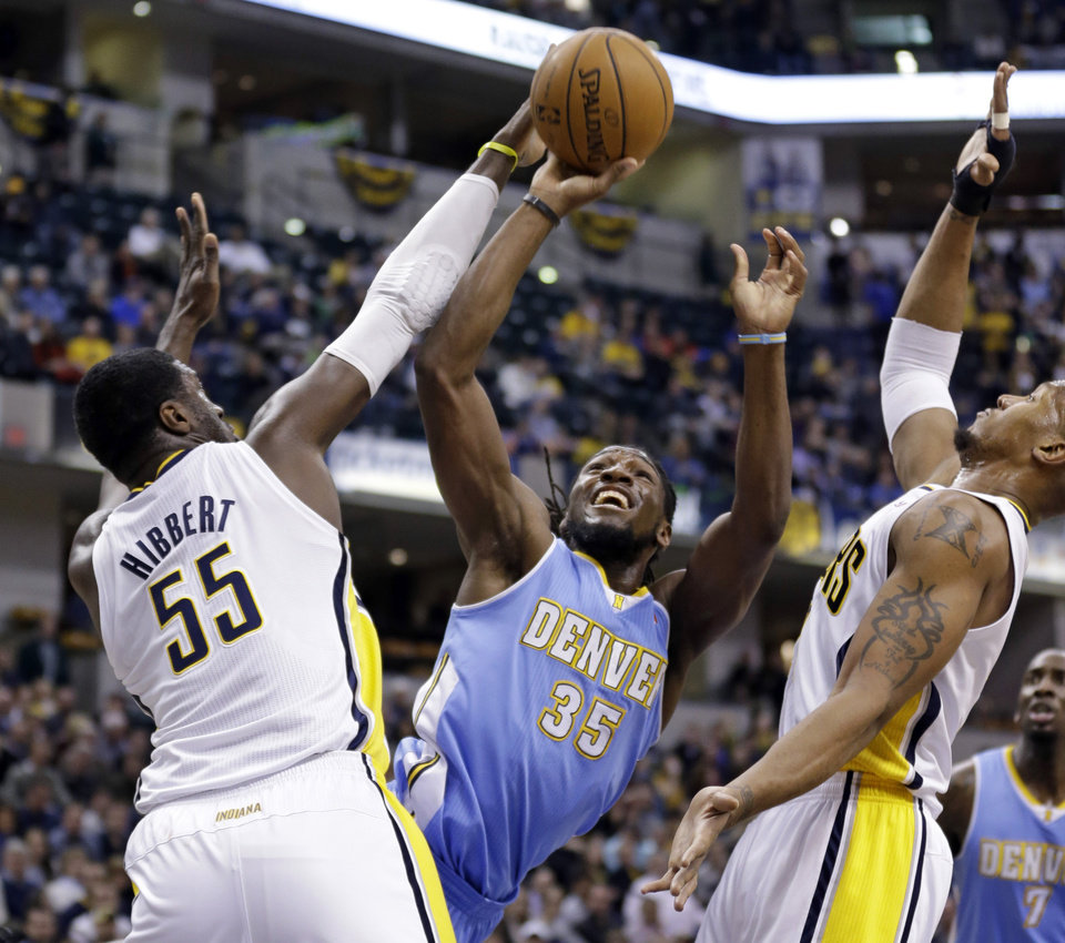 Photo - Denver Nuggets forward Kenneth Faried (35) shoots between Indiana Pacers center Roy Hibbert (55) and David West in the first half of an NBA basketball game in Indianapolis, Monday, Feb. 10, 2014. (AP Photo/Michael Conroy)