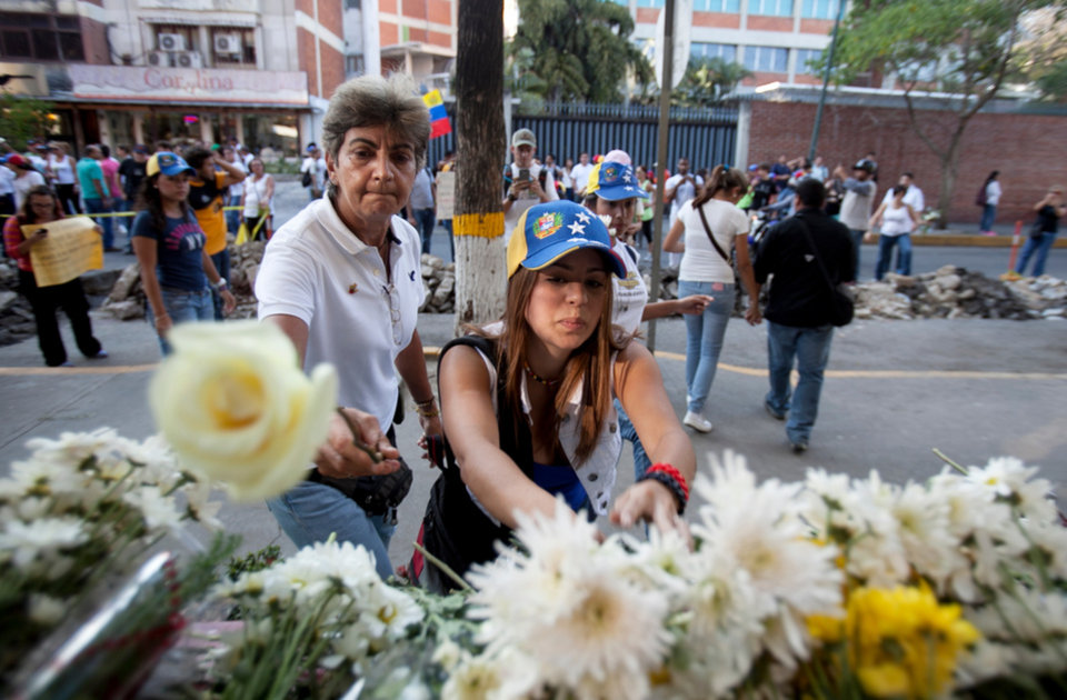 Photo - Opposition demonstrators place flowers at the entrance to the Venezuelan Military Industries (CAVIM) in Caracas, Venezuela, Thursday, Feb. 20, 2014. Venezuelan opposition leaders condemned the government Thursday for its heavy-handed attempt to subdue a protest movement with nighttime sweeps that have turned many parts of the country into dangerous free-fire zones. (AP Photo/Alejandro Cegarra)