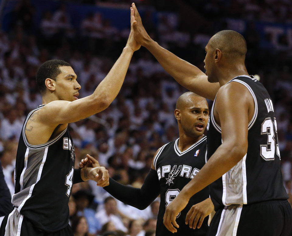 Photo - From left, San Antonio Spurs' Danny Green, Patty Mills, and Boris Diaw celebrate during the second half against the Oklahoma City Thunder in Game 6 of the Western Conference finals NBA basketball playoff series in Oklahoma City, Saturday, May 31, 2014. (AP Photo/Sue Ogrocki)