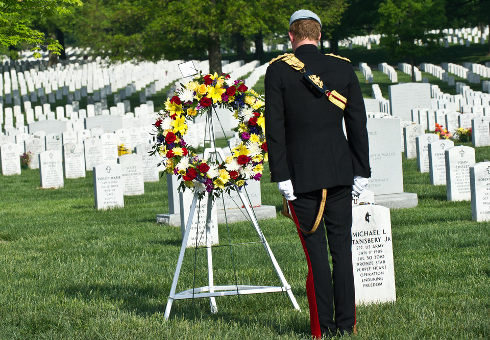 Photo - Prince Harry of Britain lays a wreath at Section 60 of Arlington National Cemetery, where veterans of the wars in Iraq and Afghanistan are buried, in Virginia on May 10, 2013.    (AP PHOTO/Nicholas Kamm, Pool)