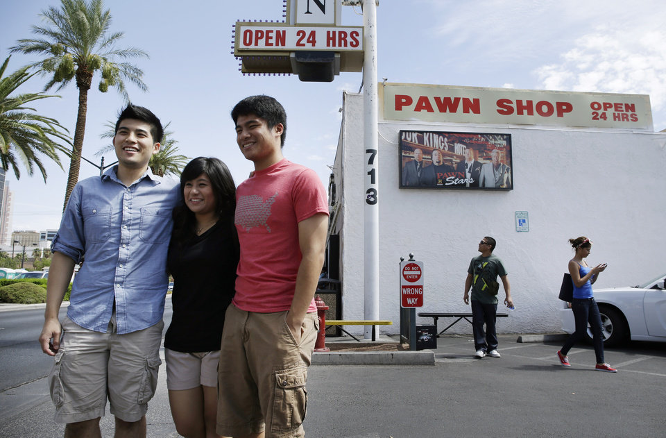 Photo - From left, Melvin Effendi, Caylin Effendi and Delwyn Effendi have their picture taken at the Gold & Silver Pawn Shop in Las Vegas Monday, July 28, 2014, in Las Vegas. Rick Harrison, owner of the pawn shop and one of the stars of the reality television series Pawn Stars, has proposed building a shopping plaza on land nearby. (AP Photo/John Locher)