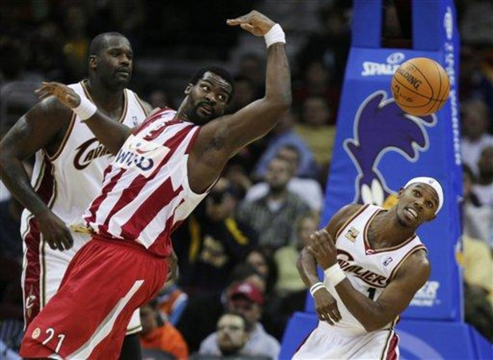 Photo -  Olympiacos Piraeus' Sofoklis Schortsanitis (21) flips a pass away from Cleveland Cavaliers' Shaquille O'Neal, left, and Daniel Gibson in the second quarter of an exhibition NBA basketball game Monday, Oct. 12, 2009, in Cleveland. (AP Photo/Mark Duncan)