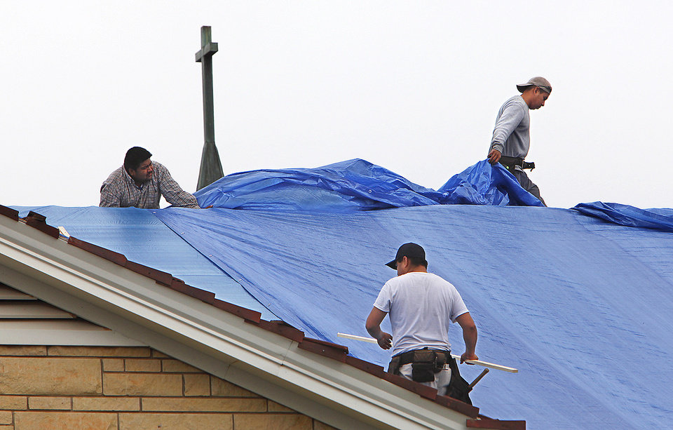 Photo - Workers cover the roof of the United Methodist Church of Nichols Hills that was damaged by Sunday's hailstorm. Photo by David McDaniel, The Oklahoman