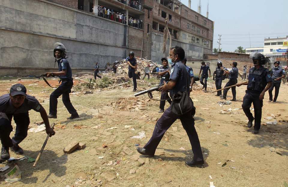 Photo - Bangladeshi police officers drive back a crowd at the site of a building that collapsed Wednesday in Savar, near Dhaka, Bangladesh, Friday, April 26, 2013. Clashes erupted after police cordoned off the building site, pushing back thousands of bystanders and relatives, after rescue workers said the crowds were hampering their work. The death toll topped 300 on Friday and it remained unclear what the final grim number would be. (AP Photo/A.M. Ahad)