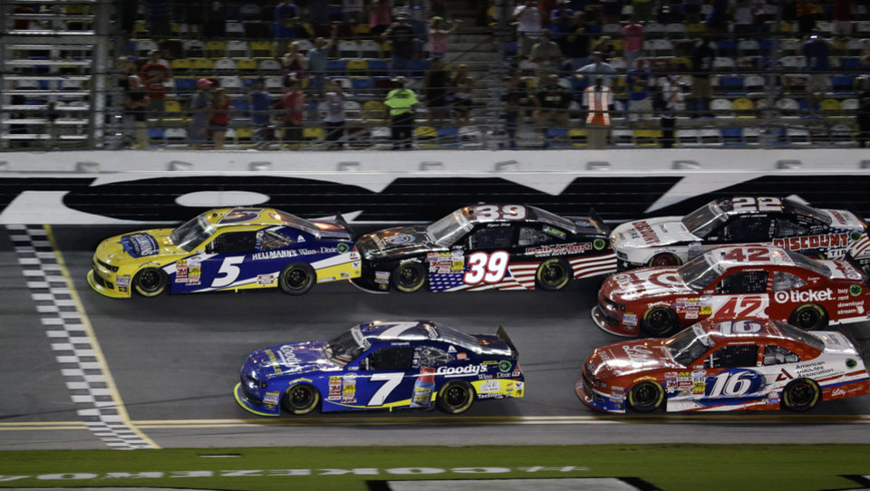 Photo - Kasey Kahne (5) makes it to the finish line ahead of Regan Smith (7) to win the NASCAR Nationwide series auto race followed by Ryan Sieg (39), Ryan Reed (16), Kyle Larson (42) and Joey Logano (22) at Daytona International Speedway in Daytona Beach, Fla., Friday, July 4, 2014. (AP Photo/John Raoux)