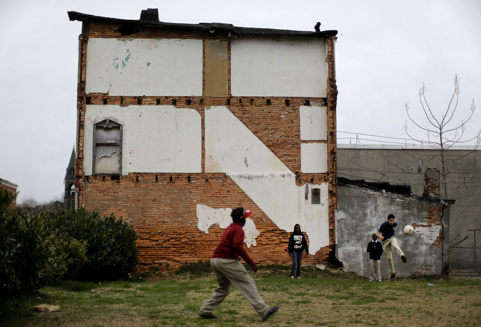 Photo - In this April 4, 2013 picture, children play kickball on a vacant lot alongside a blighted row house in Baltimore. The U.S. Census Bureau estimates that 20 percent of American children are impoverished. (AP Photo/Patrick Semansky)