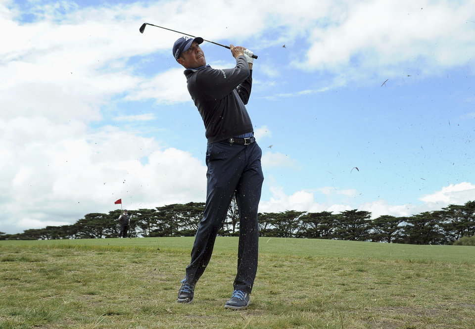 Photo - Matt Kuchar from the U.S. hits an approach shot on the second hole during the third round of the World Cup of Golf at Royal Melbourne Golf Course in Australia, Saturday, Nov. 23, 2013. (AP Photo/Andy Brownbill)