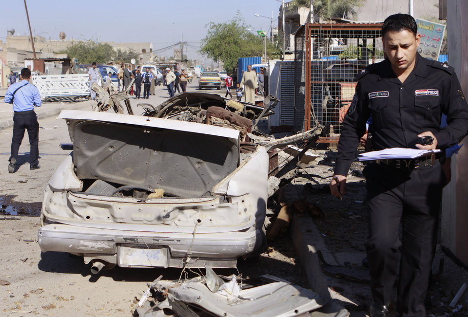 A policeman inspects the scene of a car bomb attack in the Shiite stronghold of Sadr City, Baghdad, Iraq, Tuesday, March 19, 2013. Insurgents unleashed deadly attacks Tuesday against Shiite areas in Baghdad, killing and wounding scores of people, police said. (AP Photo/ Karim Kadim)