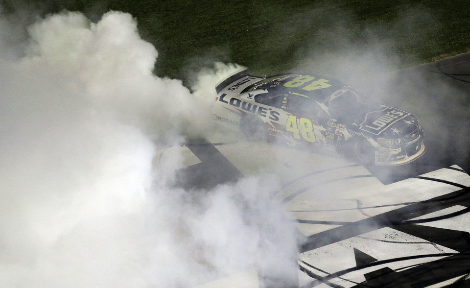 Photo - Jimmie Johnson does a burnout after winning the NASCAR Sprint Cup series Coca-Cola 600 auto race at the Charlotte Motor Speedway in Concord, N.C., Sunday, May 25, 2014. (AP Photo/Gerry Broome)