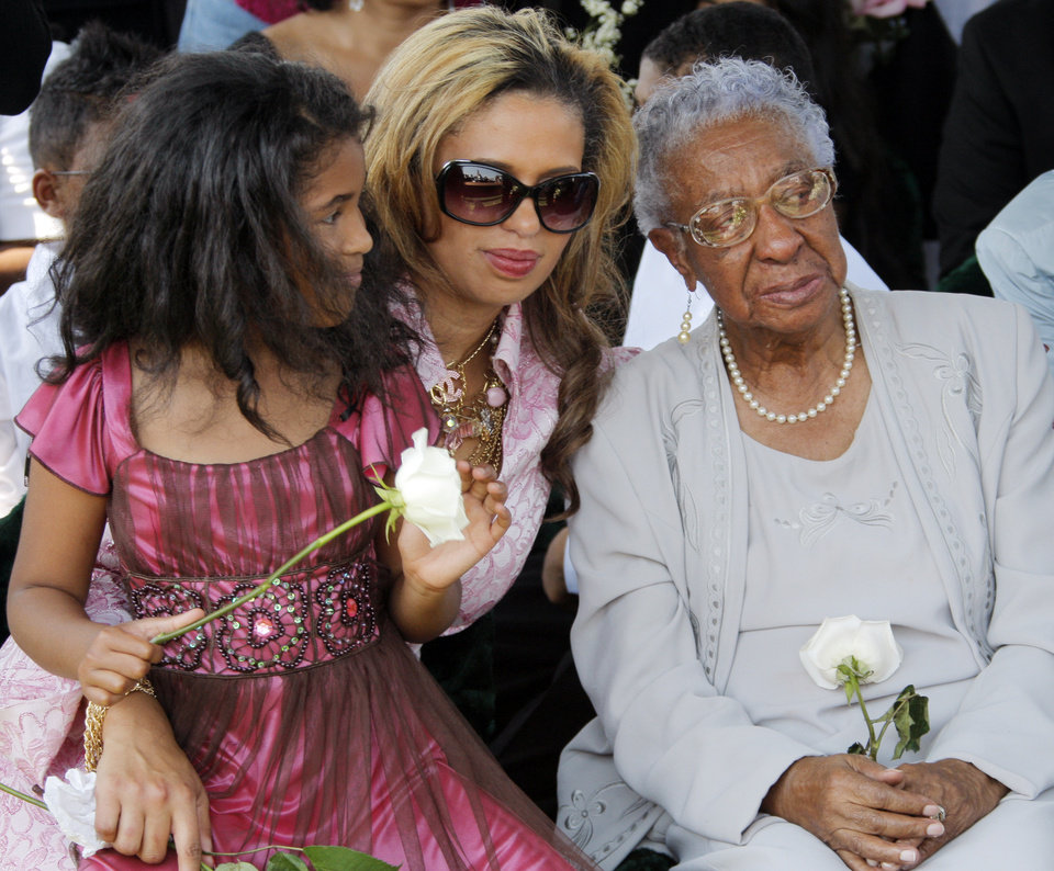 Photo - From left, Sasha Wilson, 8, granddaughter of Clara Luper, Chelle Luper Wilson, daughter of Clara Luper, and Oneita Brown, sister of Clara Luper, sit together during the graveside memorial service for civil rights activist Clara Luper at the Hillcrest Memorial Gardens cemetery in Spencer, Okla., Friday, June 17, 2011.  Luper was 88 years old when she died on June 8, 2011. Photo by Nate Billings, The Oklahoman