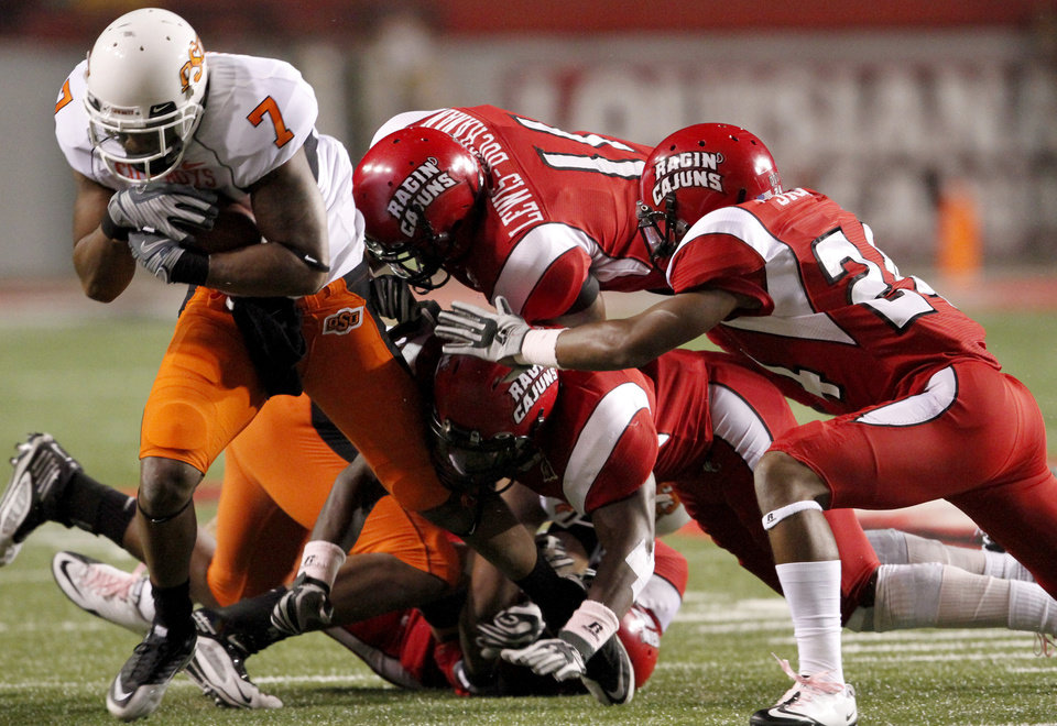 OSU's Michael Harrison fights off a group of Louisiana-Lafayette's defenders including Devon Lewis-Buchanan, top, and Lionel Stokes, right, during the football game between the University of Louisiana-Lafayette and Oklahoma State University at Cajun Field in Lafayette, La., Friday, October 8, 2010. Photo by Bryan Terry, The Oklahoman