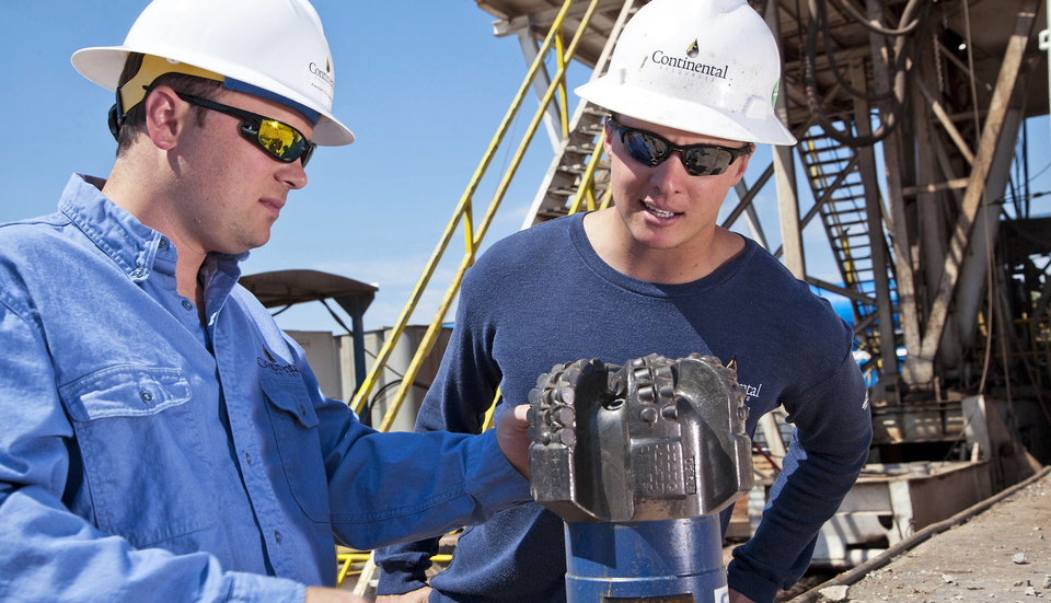 Photo - Continental Resources Inc. crews members work on a rig near Chickasha.   Photo provided