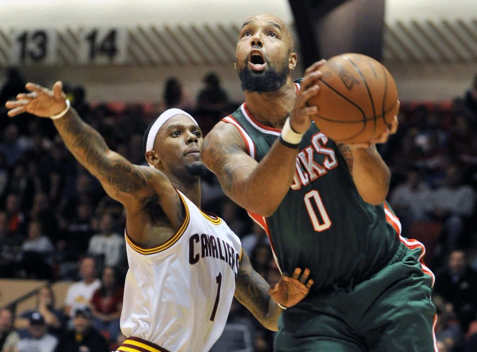 Milwaukee Bucks forward Drew Gooden (0) drives past Cleveland Cavaliers' Daniel Gibson during the second quarter of a preseason NBA basketball game, Tuesday, Oct. 9, 2012, in Canton, Ohio. (AP Photo/David Richard)