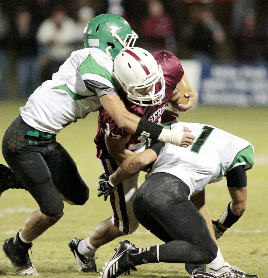 Jones players Andrew Case, left, and Randal Case (1) bring down Tuttle's Tanner Brannon in high school football on Friday, Oct. 19, 2012 in Tuttle, Okla.  Photo by Steve Sisney, The Oklahoman