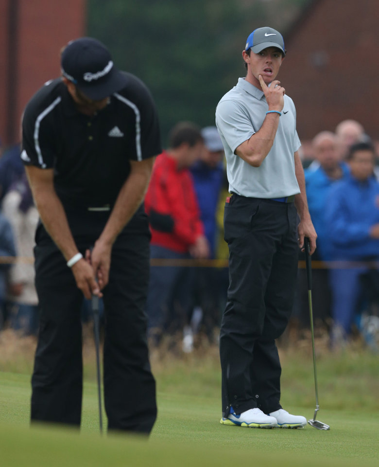Photo - Rory McIlroy of Northern Ireland, right, watches Dustin Johnson of the US putt on the 2nd green during the third day of the British Open Golf championship at the Royal Liverpool golf club, Hoylake, England, Saturday July 19, 2014. (AP Photo/Jon Super)