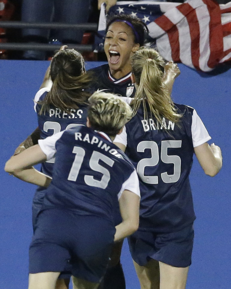 Photo - United States forward Sydney Leroux, center, celebrates after scoring her goal with teammates Christen Press (23), Morgan Brian (25) and Megan Rapinoe (15) during the second half of a soccer game against Canada, Friday, Jan. 31, 2014, in Frisco, Texas. (AP Photo/LM Otero)
