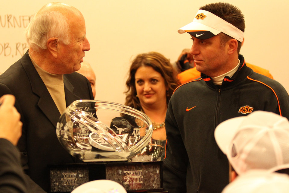 Photo - Oklahoma State football coach Mike Gundy is presented the Big 12 Championship trophy from Big 12 interim commissioner Chuck Neinas. PHOTO COURTESY OSU SPORTS INFORMATION