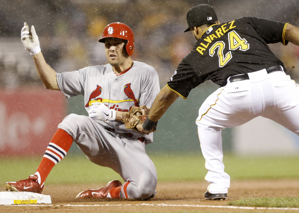Photo - St. Louis Cardinals' Peter Bourjos, left, slides into third ahead if the tag by Pittsburgh Pirates third baseman Pedro Alvarez (24) with a triple in the fourth inning of a baseball game in the rain on Friday, May 9, 2014, in Pittsburgh. (AP Photo/Keith Srakocic)