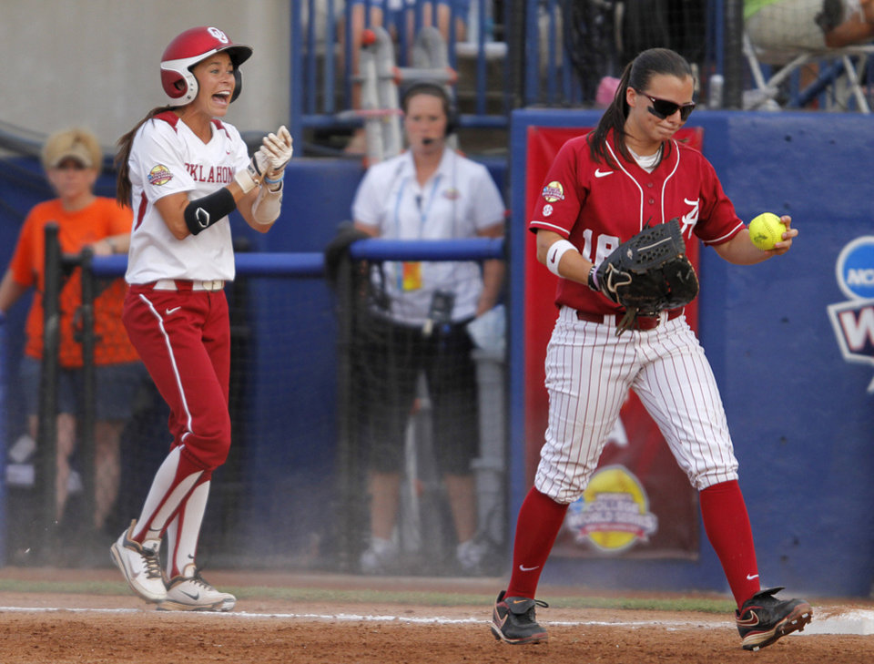 Photo - Oklahoma's Brianna Turang (2) celebrates after running into first base as Alabama's Cassie Reilly-Boccia (18) walks on during a Women's College World Series softball game between OU and Alabama at ASA Hall of Fame Stadium in Oklahoma City, Tuesday, June 5, 2012.  Photo by Garett Fisbeck, The Oklahoman