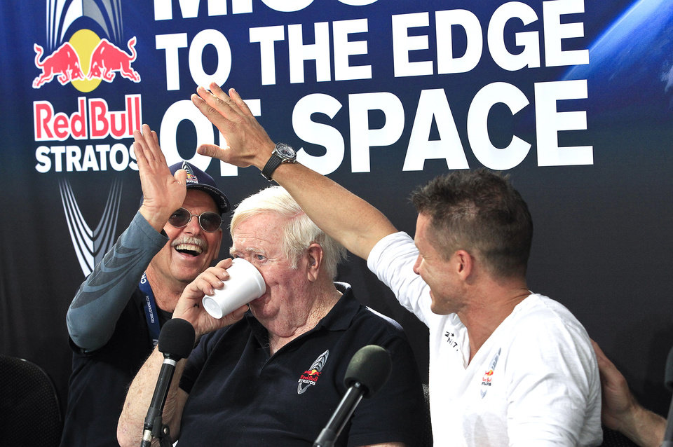 Felix Baumgartner, right, of Austria, gives a high-five to Mike Todd, left, project life support engineer, as Col. Joe Kittinger, USAF retired and who held the previous jump ascent record at 102,799 feet, takes a drink of water, during a news conference held after Baumgartner successfully jumped from a space capsule lifted by a helium balloon at a height of just over 128,000 feet above the Earth's surface, Sunday, Oct. 14, 2012, in Roswell, N.M. (AP Photo/Ross D. Franklin) ORG XMIT: NMRF130
