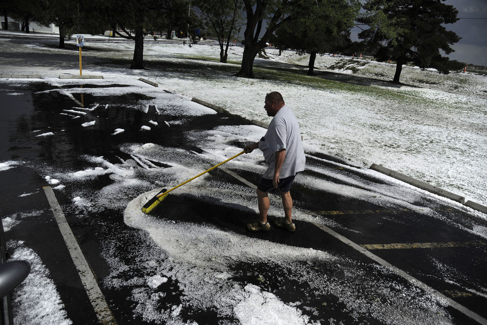 Photo - Rob Post sweeps hail and clears water after hail pounded Woodshire Mobile Park. A hail storm hit the Denver metro area on Wednesday, May 21, 2014. (AP Photo/The Denver Post, AAron Ontiveroz)