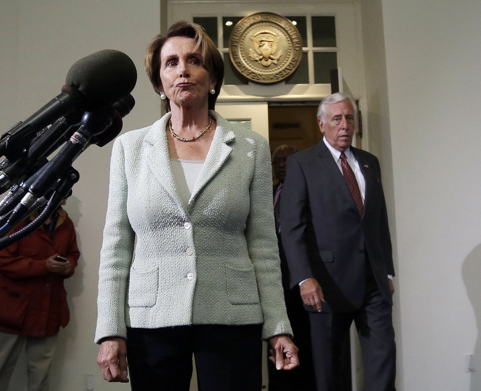 Photo - House Minority Leader Rep. Nancy Pelosi, D-Calif., left, and Minority Whip Steny Hoyer, D-Md., right, walk out of the West Wing of the White House to speak to members of the media following their meeting with President Barack Obama, Wednesday, Oct. 9, 2013, in Washington. (AP Photo/Pablo Martinez Monsivais)
