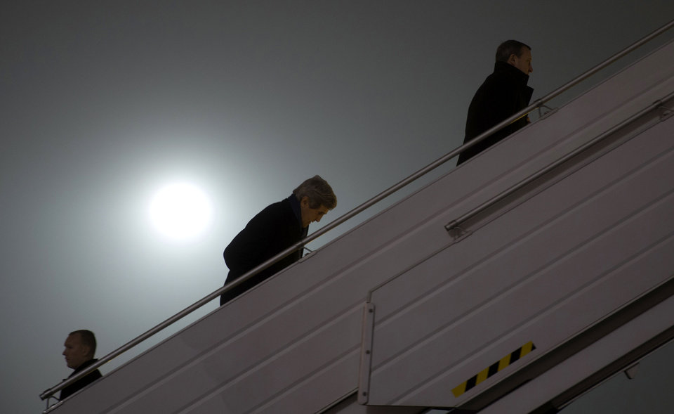 Photo - Secretary of State John Kerry, center, walks up the stairs to board his plane before his departure from Kiev, Ukraine, Tuesday, March 4, 2014. Ahead of Kerry on the stairs is Ukraine Foreign Minister Andrii Deshchytsia, who is travelling to Paris with Kerry. Kerry announced an economic package and technical assistance for Ukraine in a show of support for its new government amid escalating tensions with Russia. Kerry's visit comes as Washington and its Western allies step up pressure on Moscow to withdraw its troops from Ukraine's Crimea region or face economic sanctions and diplomatic isolation.  (AP Photo/Kevin Lamarque, Pool)