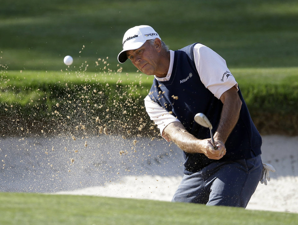 Photo - Tom Lehman hits from the sand on the 18th green during the final round of the Greater Gwinnett Championship golf tournament, Sunday, April 21, 2013, in Duluth, Ga. (AP Photo/John Bazemore)