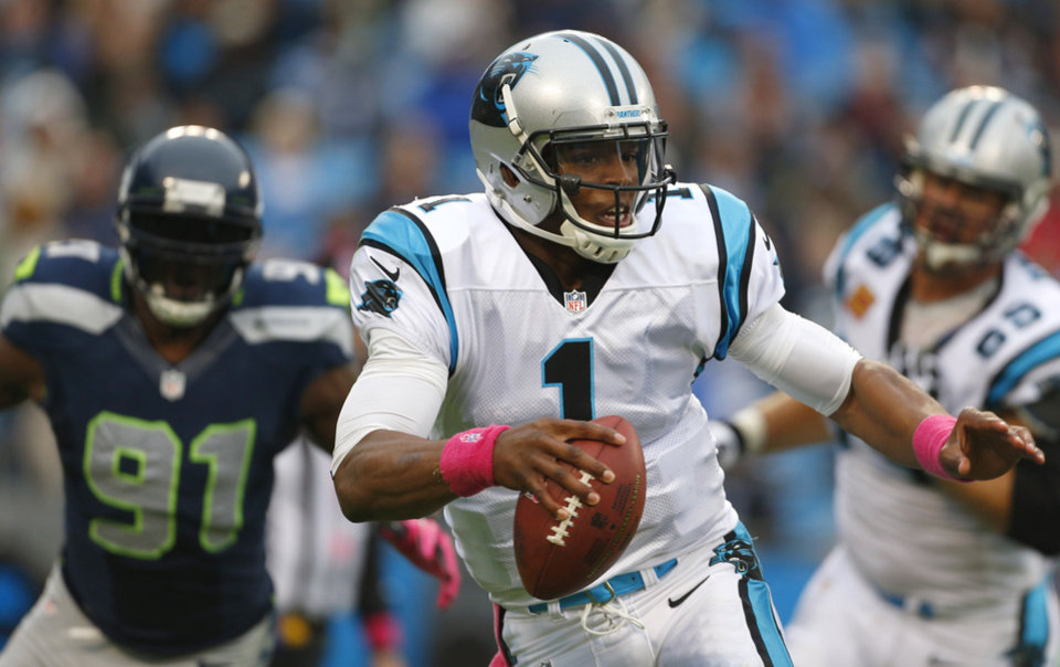 Carolina Panthers' Cam Newton (1) scrambles as Seattle Seahawks' Chris Clemons (91) chases during the second quarter of an NFL football game in Charlotte, N.C., Sunday, Oct. 7, 2012. (AP Photo/Bob Leverone)