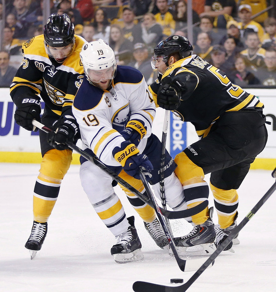 Photo - Buffalo Sabres' Cody Hodgson (19) battles Boston Bruins' Jordan Caron (38) and Johnny Boychuk (55) for the puck during the first period of an NHL hockey game in Boston, Saturday, April 12, 2014. (AP Photo/Michael Dwyer)