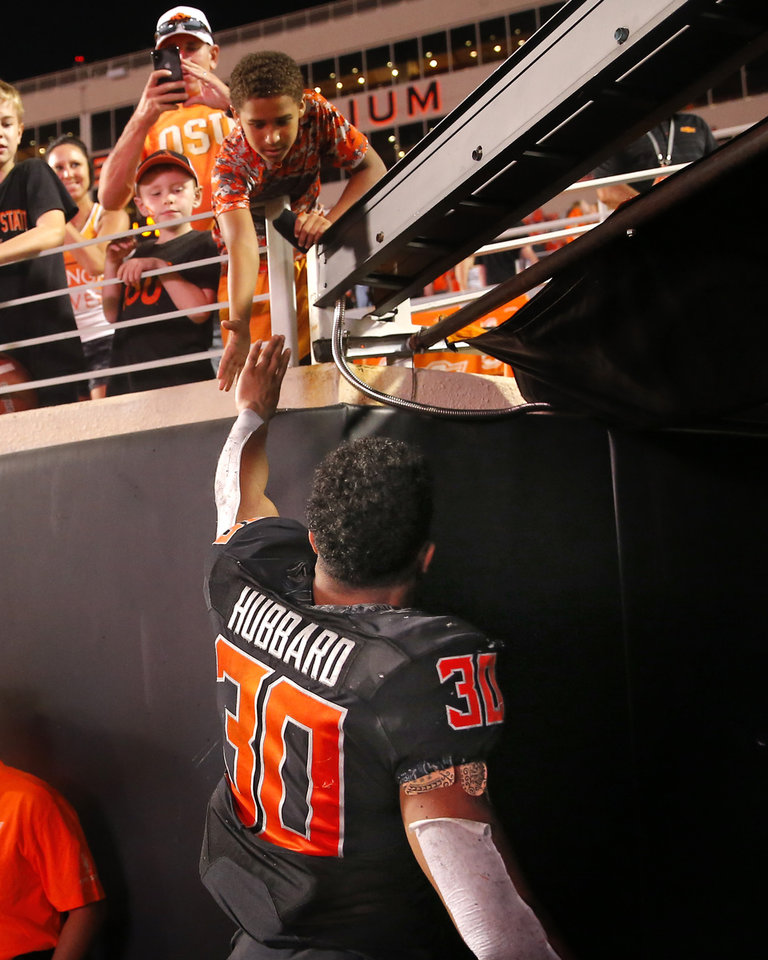 Photo - Oklahoma State's Chuba Hubbard (30) high fives fans following the college football game between the Oklahoma State Cowboys and the Kansas State Wildcats at Boone Pickens Stadium in Stillwater, Okla., Saturday, Sept. 28, 2019.  OSU won 26-13. [Sarah Phipps/The Oklahoman]