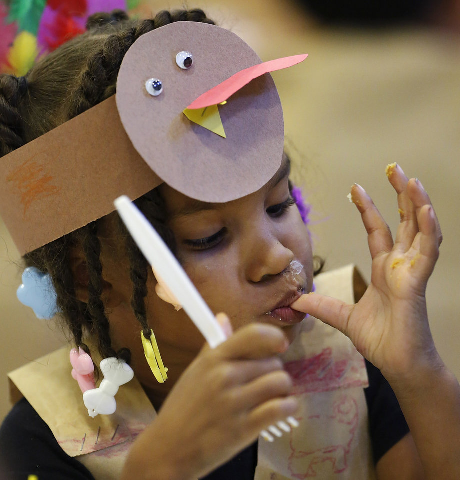 Cynih (cq) Robins (cq) licks pie from her fingers. Kindergarten students at Eugene Field Elementary School in Oklahoma City have been learning about Thanksgiving traditions and the history of the national holiday in America. Their teachers helped them make paper sack vests and turkey head pieces to wear. To celebrate the end of the Thanksgiving lesson and reward the students for working so hard, about 80 students in the four kindergarten classes held a pumpkin pie break in the cafeteria Tuesday afternoon, Nov. 20, 2012. The students dressed in their creative paper sack turkey vests and head dresses. Photo by Jim Beckel, The Oklahoman