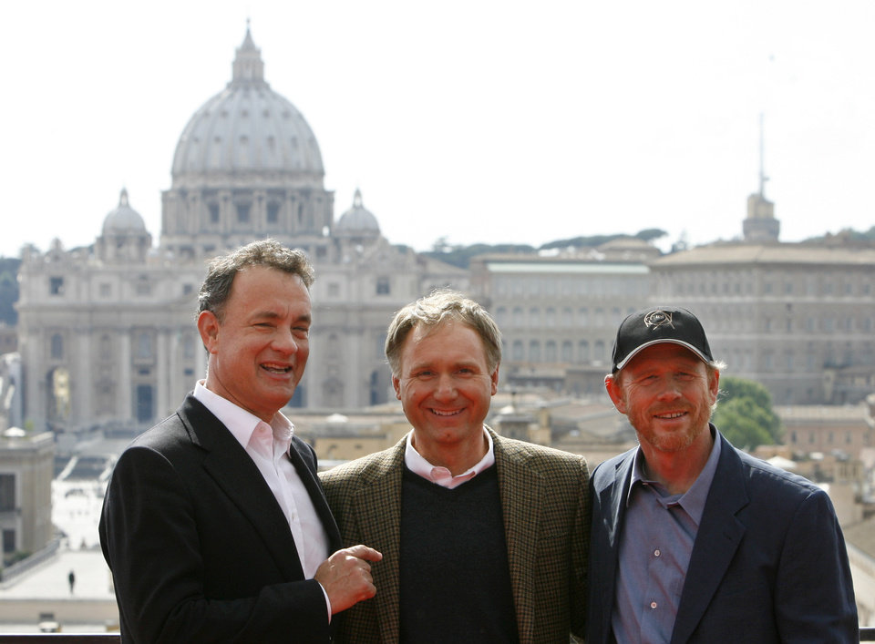 Photo - Actor Tom Hanks, left, shares a laugh with writer Dan Brown, center, and director Ron Howard as they pose in front of St. Peter's Basilica during the photo call for the World Premiere of the movie