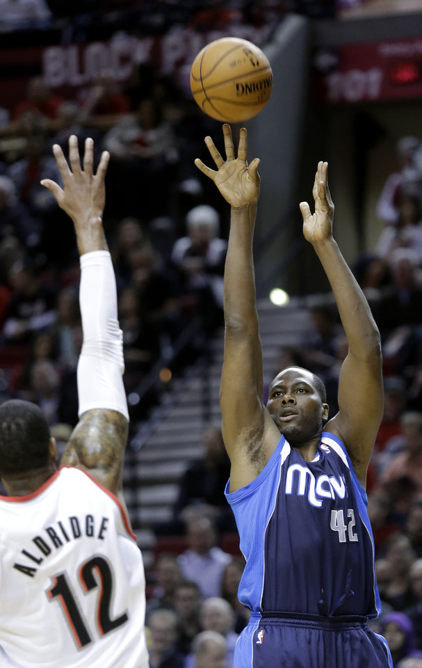 Dallas Mavericks forward Elton Brand, right, shoots over Portland Trail Blazers forward LaMarcus Aldridge during the first quarter of an NBA basketball game in Portland, Ore., Tuesday, Jan. 29, 2013.(AP Photo/Don Ryan)