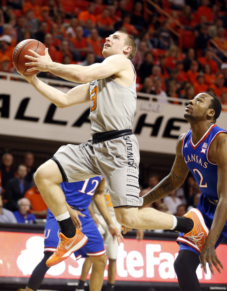 Photo - Phil Forte III (13) drives to the basket in front of Kansas' Cliff Alexander (2) during the men's college basketball game between Oklahoma State University and the University of Kansas at Gallagher-Iba Arena in Stillwater, Okla.,  Saturday, Feb. 7, 2015. Photo by Sarah Phipps, The Oklahoman