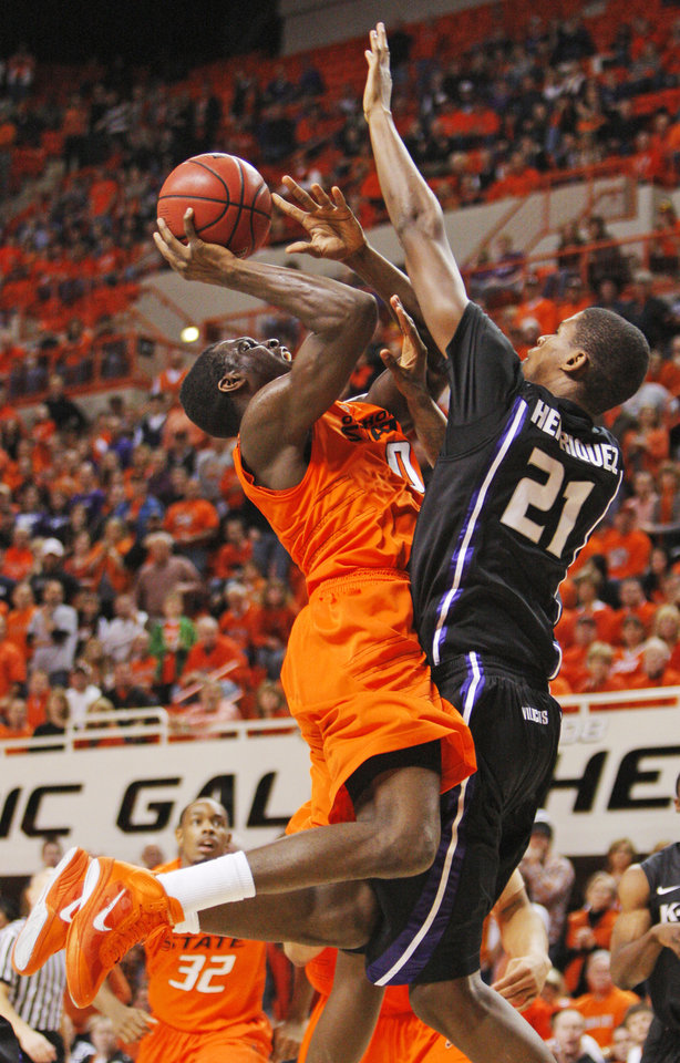 Photo - OSU's Jean-Paul Olukemi (0) is fouled by Jordan Henriquez-Roberts (21) of KSU as Olukemi takes a shot during the men's college basketball game between Oklahoma State University (OSU) and Kansas State University (KSU) at Gallagher-Iba Arena in Stillwater, Okla., Saturday, January 8, 2011. OSU won, 76-62. Photo by Nate Billings, The Oklahoman