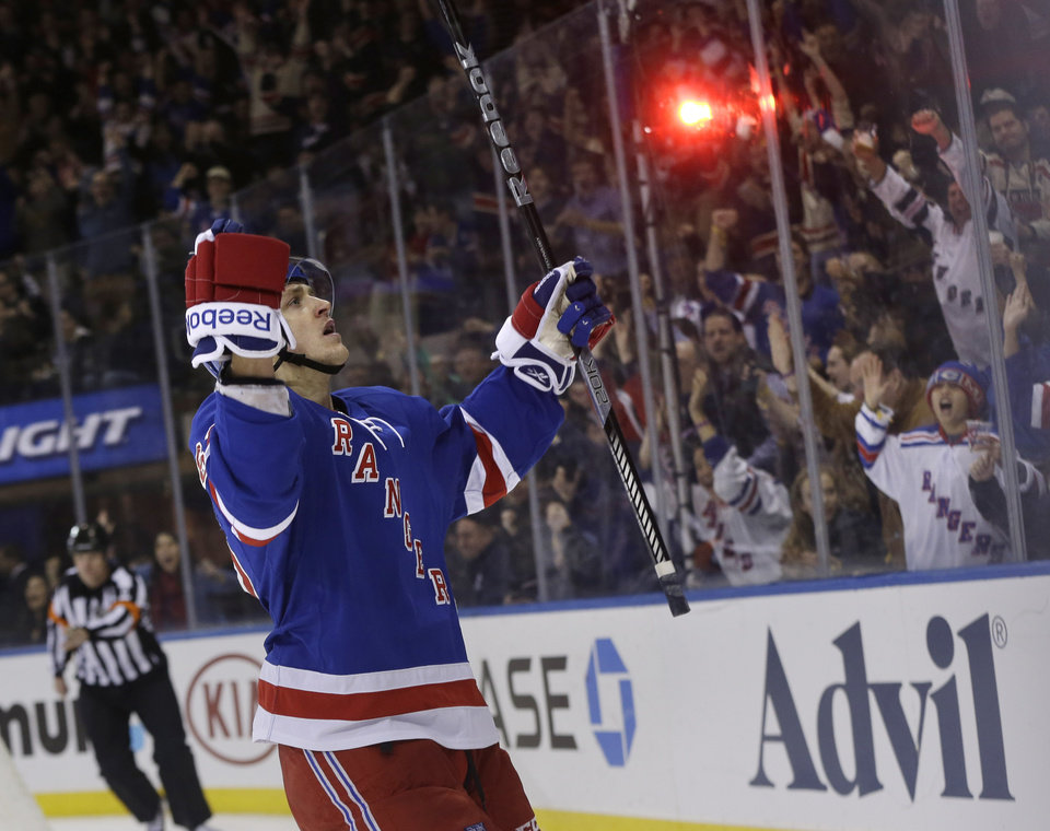 Photo - New York Rangers' Carl Hagelin, left, reacts after scoring during the second period of an NHL hockey game against the Minnesota Wild, Sunday, Dec. 22, 2013, in New York. (AP Photo/Seth Wenig)