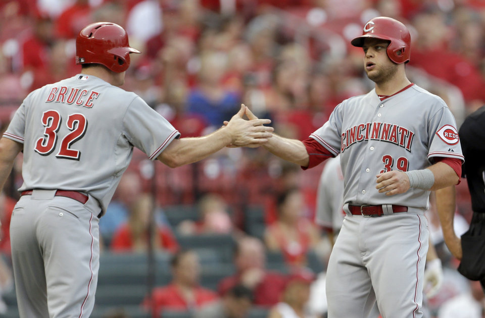 Photo - Cincinnati Reds' Jay Bruce, left, and Devin Mesoraco celebrate after scoring on a two-run triple by Zack Cozart during the second inning of a baseball game against the St. Louis Cardinals Monday, Aug. 26, 2013, in St. Louis. (AP Photo/Jeff Roberson)