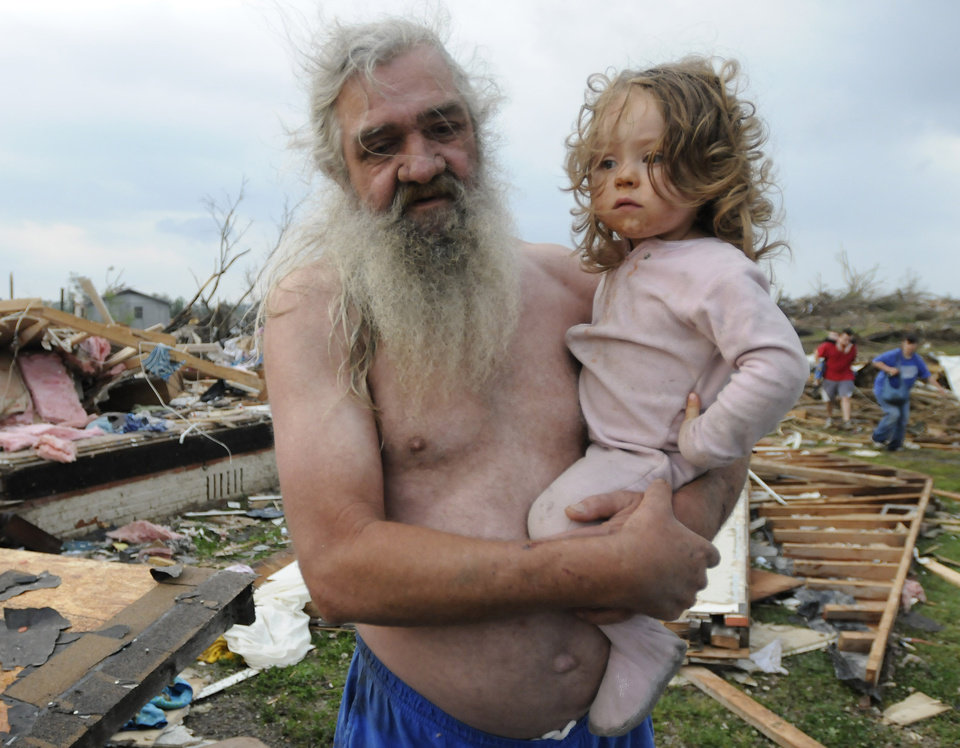 Photo - Willie Hyde holds his grand daughter 2-years-old Sierra Goldsmith near where their house stood in Concord Ala., after what appeared to be a tornado ripped through parts of the town late Wednesday, April 27, 2011. The damage in the area is extensive with homes and businesses destroyed and people injured.  (AP Photo/Birmingham News, Jeff Roberts)