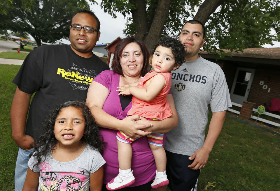 Photo - Kaylee Sanchez, 6, her father Eli Sanchez, mother Maria Sanchez, sister Ellie Sanchez, 1, and uncle Miguel Blanco pose for a photo in front of the Sanchez's home in the Plaza Towers housing addtion in Moore. Photo by Nate Billings, The Oklahoman   NATE BILLINGS - NATE BILLINGS
