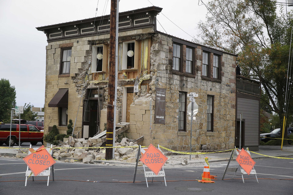 Photo - Signs and caution tape block the street in front of the earthquake-damaged Vintner's Collective multi-winery tasting room Monday, Aug. 25, 2014, in Napa, Calif. The building dates from the late 1800s. The San Francisco Bay Area's strongest earthquake in 25 years struck the heart of California's wine country early Sunday, igniting gas-fed fires, damaging some of the region's famed wineries and historic buildings, and sending dozens of people to hospitals. (AP Photo/Eric Risberg)