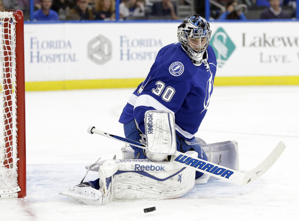 Photo - Tampa Bay Lightning goalie Ben Bishop (30) kicks aside a shot by the Phoenix Coyotes during the first period of an NHL hockey game, Monday, March 10, 2014, in Tampa, Fla. (AP Photo/Chris O'Meara)