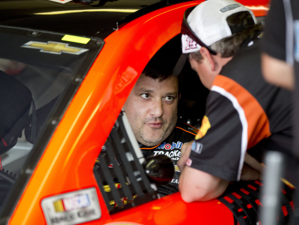 Photo - NASCAR driver Tony Stewart talks with a crew member during practice for Sunday's NASCAR auto race at Atlanta Motor Speedway in Hampton, Ga., Friday, Aug. 29, 2014. Sunday's race will be his first since his car struck and killed a fellow driver during a sprint race in New York three weeks ago. (AP Photo/John Bazemore)