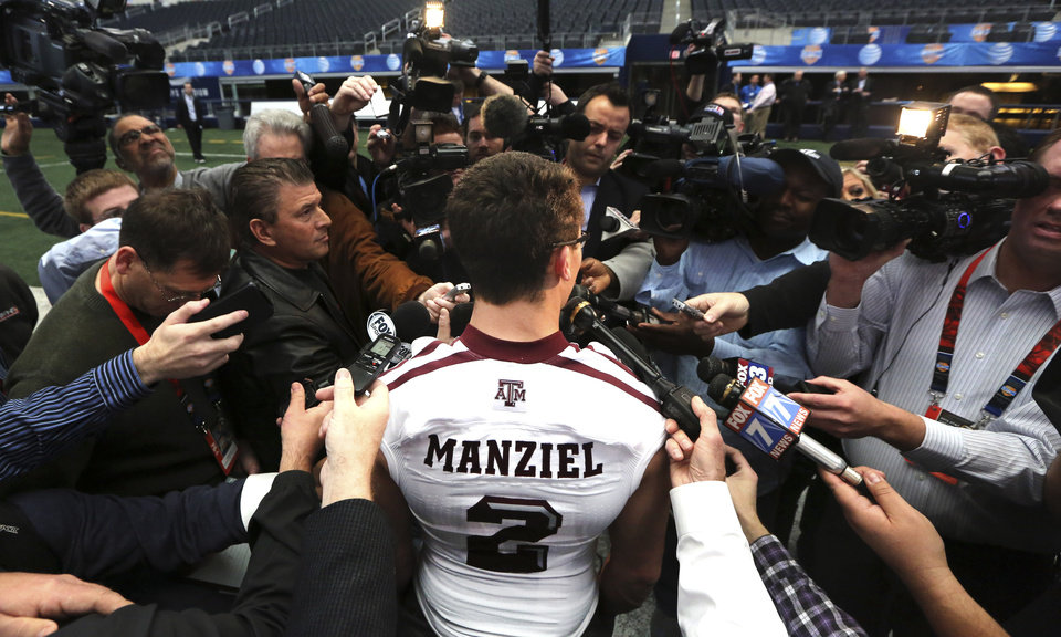 Photo - Texas A&M quarterback Johnny Manziel (2) talks to reporters during media day for the Cotton Bowl Classic NCAA college football game at Cowboys Stadium, Sunday, Dec. 30, 2012, in Arlington, Texas. Oklahoma and Texas A&M are scheduled to play on Jan. 4, 2013. (AP Photo/LM Otero) ORG XMIT: TXMO103