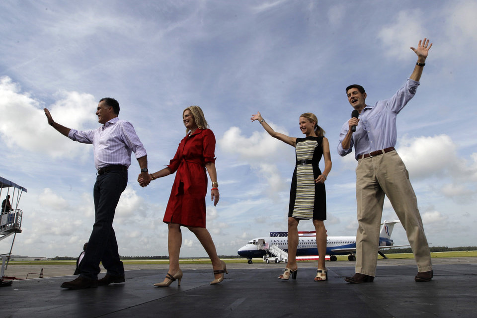 Photo -   From left, Republican presidential nominee Mitt Romney, his wife Ann and his vice presidential running mate Rep. Paul Ryan, right, with his wife Janna, wave at supporters during a campaign event at Lakeland Linder Regional Airport, Friday, Aug. 31, 2012, Lakeland, Fla. (AP Photo/Mary Altaffer)