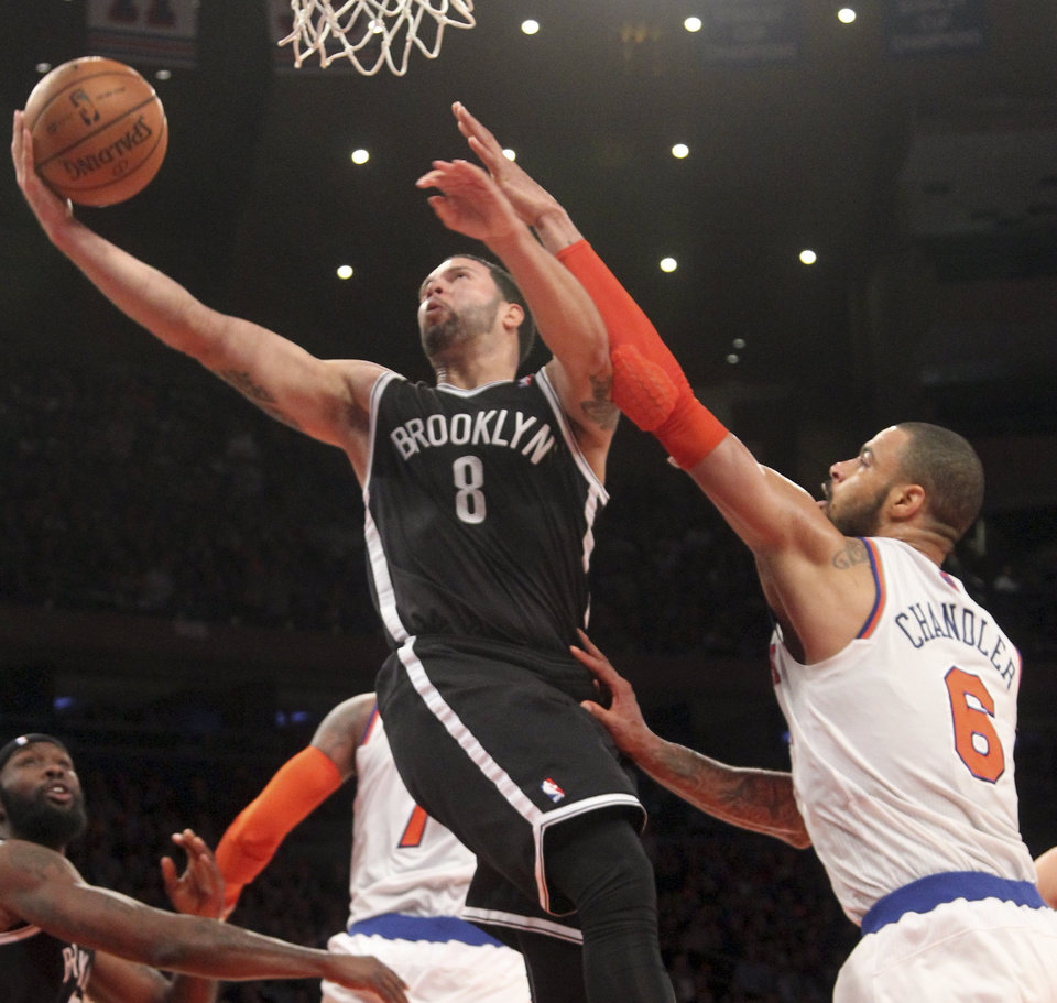 Photo - Brooklyn Nets' Deron Williams (8) goes to the basket against New York Knicks' Tyson Chandler, right, during the second half of NBA basketball game on Wednesday, Dec. 19, 2012, at Madison Square Garden in New York. The Knicks defeated the Nets 100-86.  (AP Photo/Mary Altaffer)