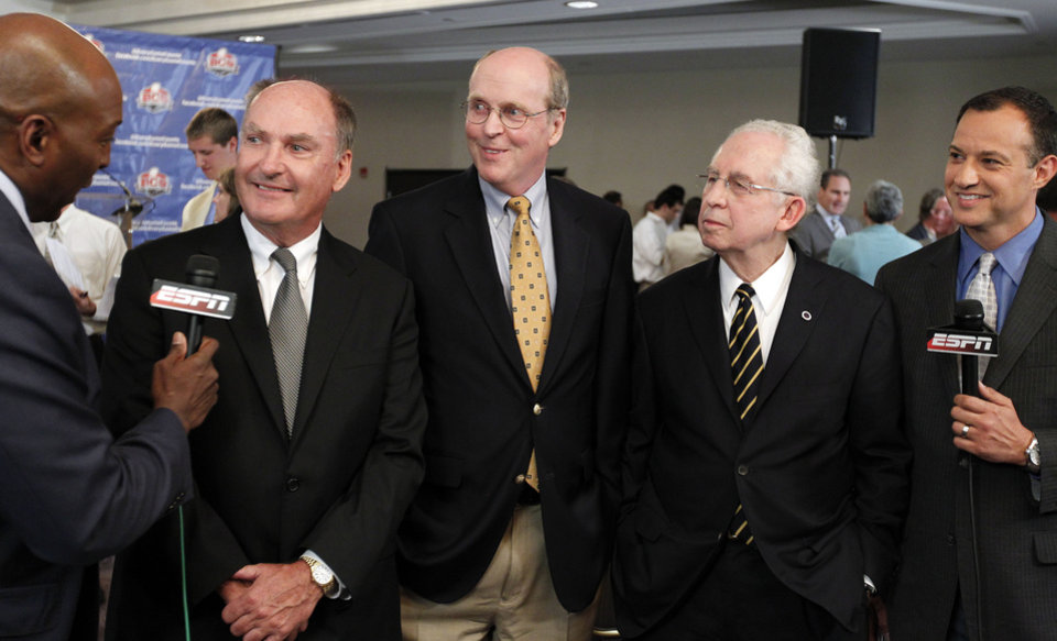 Photo -   Big Ten Commissioner Jim Delany, second from left, BCS executive director Bill Hancock, center, and SEC Commissioner Mike Slive, second from right, smile during an interview after a BCS presidential oversight committee meeting and media availability, Tuesday, June 26, 2012, in Washington. A committee of university presidents on Tuesday approved the BCS commissioners' plan for a four-team playoff to start in the 2014 season. (AP Photo/Alex Brandon)