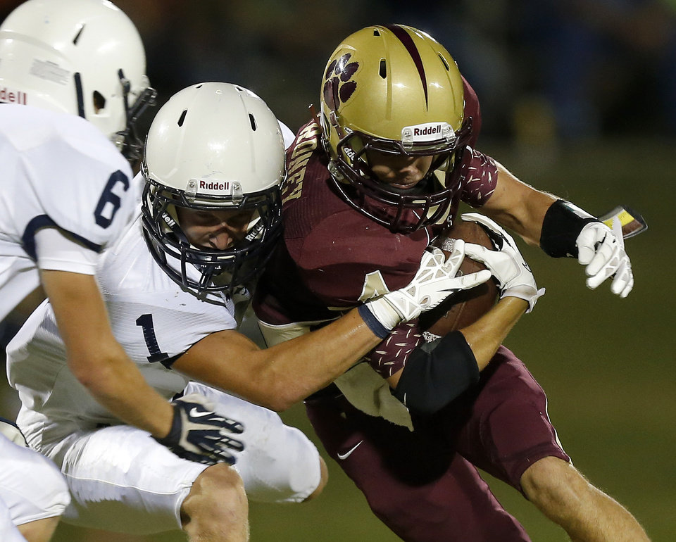 Cahsion's Peyton Maroney is brought down by Minco's Joe Mitchell during their high school football game in Cashion, Okla., Friday, Sept. 27, 2013. Photo by Bryan Terry, The Oklahoman