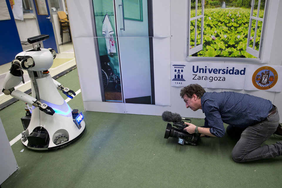 Photo - A cameraman films Amigo, a white robot the size of a person, who uses information gathered by other robots to move towards a table to pick up a carton of milk and deliver it to an imaginary patient in a mock hospital room at the Technical University of Eindhoven, Netherlands, Wednesday Jan. 15, 2014. A group of five of Europe's top technical universities, together with technology conglomerate Royal Philips NV, are launching an open-source system dubbed